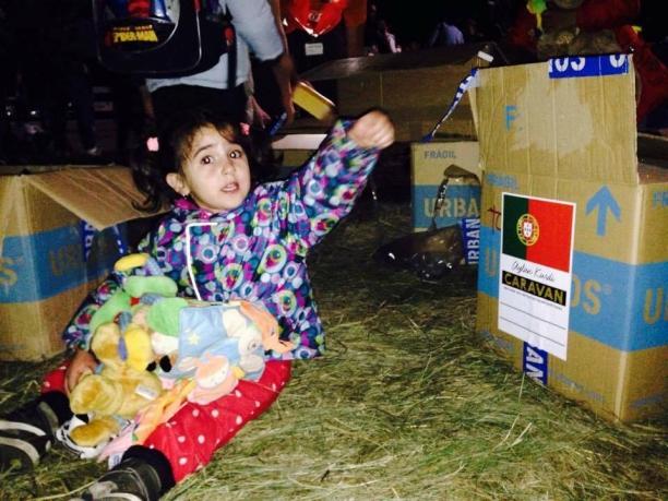 Criança refugiada é clicada junto a caixa de donativos da caravana Crédito: Divulgação/Aylan Kurdi Caravan