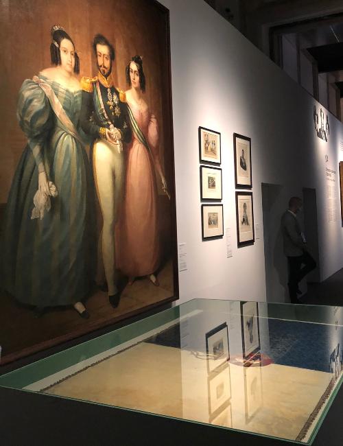 Pintura de D. Maria 2ª junto ao pai, D. Pedro 1º, e à madrasta, D. Amélia. EM frente, bandeira de Portugal bordada pela própria rainha | Foto: Giuliana Miranda/Folhapress